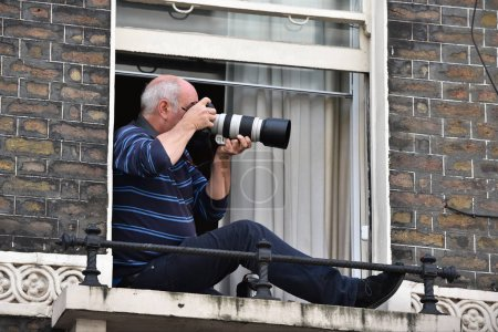 London, UK - March 4, 2017: photgrapher siting at window as protesters rally in support of NHS