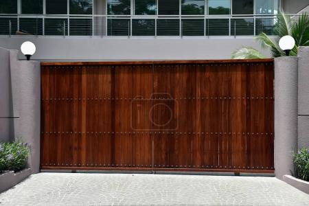 Photo for House exterior with brown automatic gates, grey fence, street lights and plants - Royalty Free Image