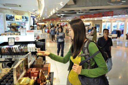 Bangkok, Thailand - June 28, 2012: air traveler browsing duty free shop at Suvarnabhumi Airport