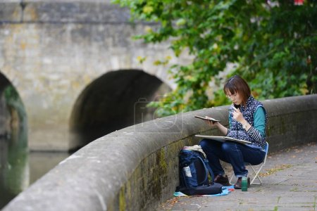 Photo for Girl sitting on the bench and reading a book - Royalty Free Image