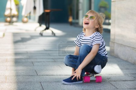 Pretty little boy on a skate board. Emotional kid outdoors. Cute