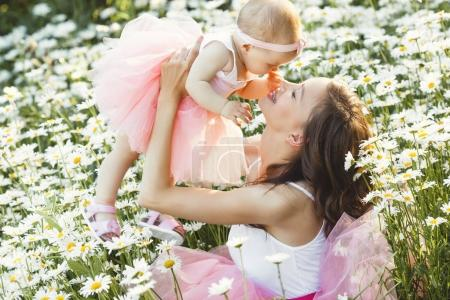 Photo for Young pretty mother with her little baby outdoors. Beautiful woman with her daughter on the nature. infant child with her parent on the chamomile field - Royalty Free Image
