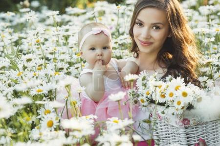 Young pretty mother with her little baby outdoors. Beautiful wom