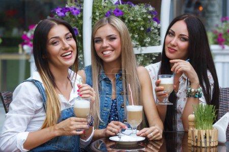 Photo pour Un groupe de trois jeunes jolies petites amies qui boivent du café au café. Jolies femmes gaies qui s'amusent à la cafétéria . - image libre de droit
