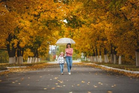Photo for Cheerful mother and her little daughter having fun together in the autumn background under the umbrella. Happy family in the fall background. Cute girls with umbrella. - Royalty Free Image