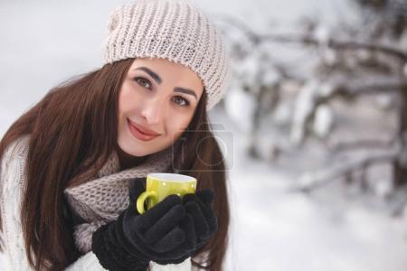 Photo pour Jolie fille dans les bois en fond d'hiver avec tasse de thé. Belle femme gaie buvant du café à l'extérieur. Gros plan portrait d'une belle dame - image libre de droit