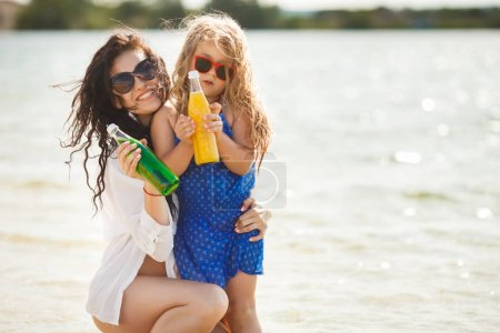Photo for Young mother with daughter holding bottles with lemonade on beach - Royalty Free Image