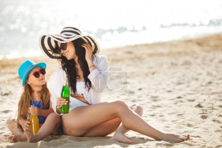Young mother with daughter sitting on beach and drinking lemonade