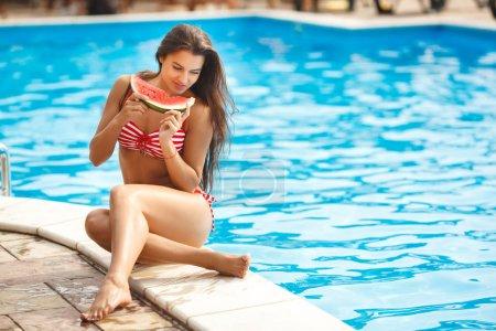 woman in striped bikini eating watermelon near swimming pool