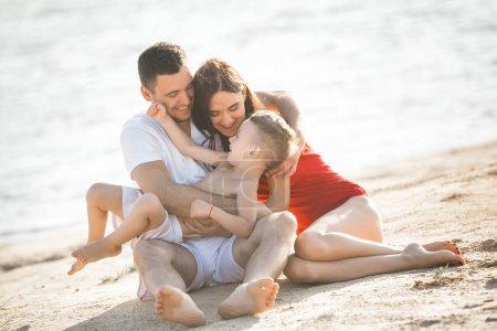 Photo pour Jeune famille, passer du bon temps avec fils sur la plage près de l'eau - image libre de droit