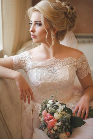 Tender young bride in elegant wedding dress holding wedding bouquet