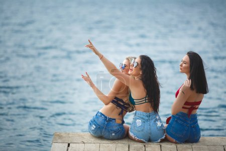 Young attractive cheerful women on the pier having fun