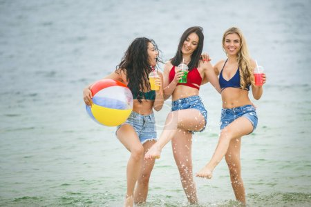 Young attractive women at the beach party having fun. Pretty girls having fun
