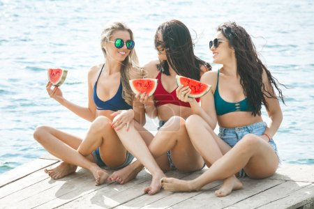 Group of young cheerful girls having fun on the pier eating watermelon and enjoying sun