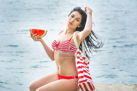 Young attractive woman on the beach with watermelon