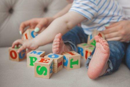 Unrecognazable child plaing with abc cubes