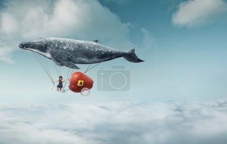 Photo pour Emmène-moi au concept du rêve. Deux jolies petites filles asiatiques sur un vélo tandem, l'une des filles assise à l'intérieur d'une pomme rouge géante, s'accrochant à une grosse baleine grise et volant au-dessus des nuages - image libre de droit