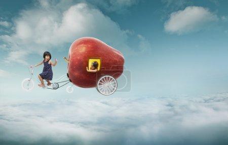 Photo pour Emmenez-moi au concept du rêve. Deux jolies petites filles asiatiques sur un vélo tandem, l'une des filles assise à l'intérieur d'une pomme rouge géante. Ciel nuageux fond - image libre de droit