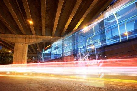 Photo pour Bus rapide la nuit et sentiers de lumière floue à grande vitesse - image libre de droit