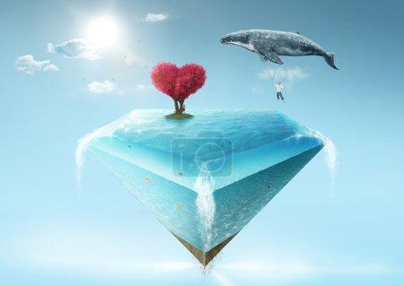 Photo pour Emmène-moi au concept du rêve. Jeune homme s'accrochant à une grosse baleine grise et volant vers un diamant aquatique bleu avec un arbre rouge en forme de coeur dessus - image libre de droit