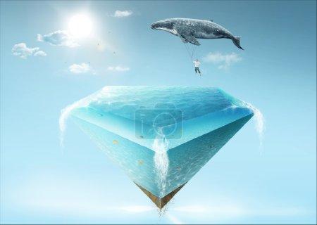 Photo pour Emmène-moi au concept du rêve. Jeune homme s'accrochant à une grosse baleine grise et volant au-dessus d'un beau diamant aquatique bleu - image libre de droit