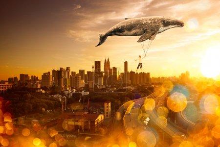Photo pour Emmène-moi au concept du rêve. Jeune homme s'accrochant à une grosse baleine grise et survolant les toits du paysage urbain - image libre de droit