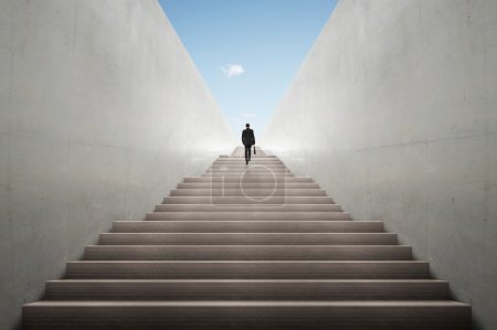Ambitions concept with businessman climbing stairs