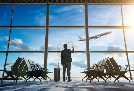 businessman waving at airport