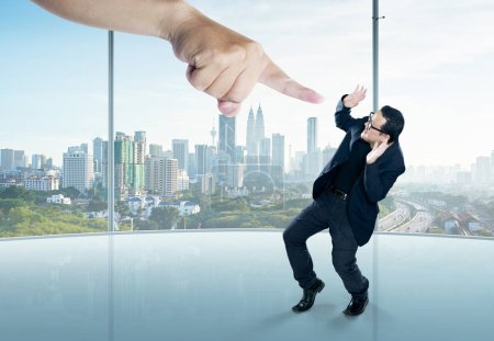 Photo for Scared businessman full-height in a scare pose and a giant hand pointing at him, on the office background. Business and management. Employment issues. Getting fired. Being told off. - Royalty Free Image
