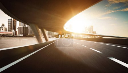Photo for Highway and bridge overpass motion blur with city skyline background - Royalty Free Image