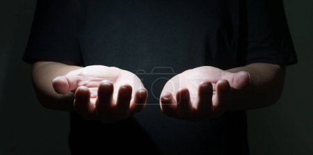Photo for Male Praying Hands in black background in dramatic light - Royalty Free Image