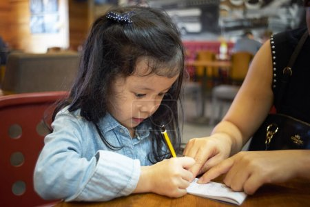Mother teaching girl writing
