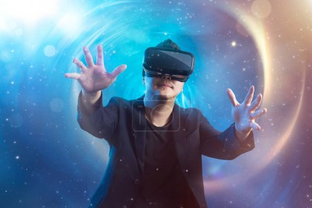 Photo for The young man wearing virtual reality goggles with amazing cosmic futuristic space virtual imaging background . - Royalty Free Image