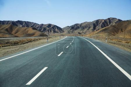 Photo for Long empty asphalt road in desert with  clear blue sky . - Royalty Free Image