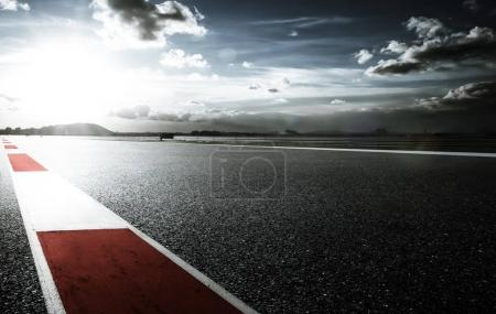 Photo for Racetrack with red and white safety sideline ,dramatic cloudy sky and cold mood filter apply . - Royalty Free Image