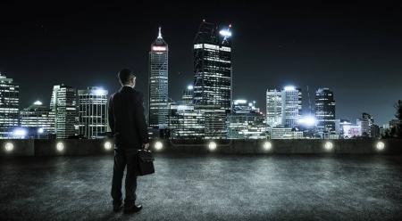 Photo pour Homme d'affaires regardant et pensant sur le toit avec fond skyline ville moderne, scène de nuit - image libre de droit