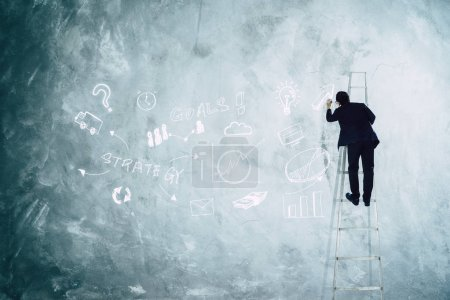 Man drawing development graph strategy on grey wall .