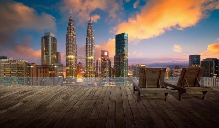 Wooden balcony terrace with wooden relax chair , kuala lumpur city skyline background , night scene .