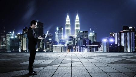 Photo for Businessman using laptop with cityscape background , night scene . - Royalty Free Image