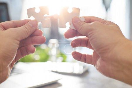 businessman connecting puzzle pieces