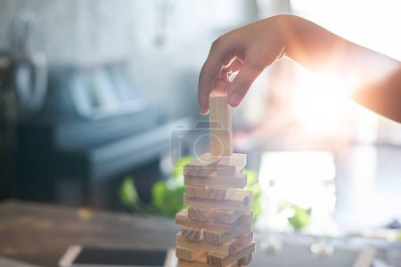 kid playing a blocks wood tower