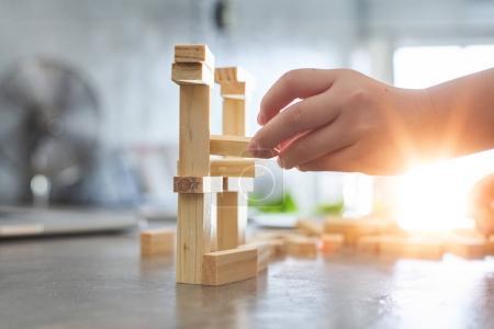 kid playing a blocks wood tower