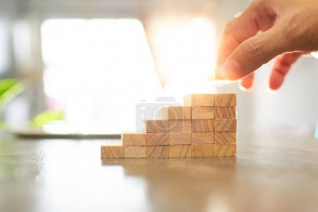 Photo for Hand of engineer playing a wood block podiums. Growth in business and goal concept. - Royalty Free Image