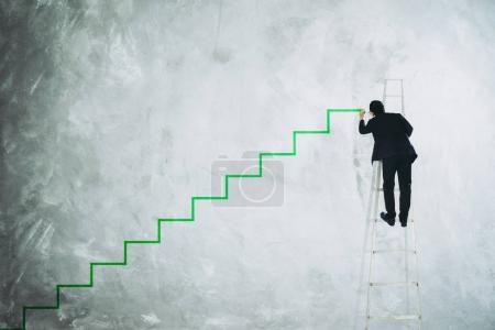 Photo for Man drawing stair on grey wall . - Royalty Free Image