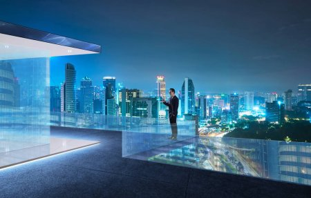 Businessman use digital device stand at modern rooftop with beautiful city skyline , night scene .