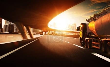 Truck on the road with  motion blur with city skyline background . Sunset scene .