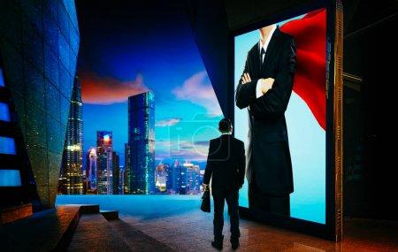 Photo pour Jeune homme d'affaires regardant le héros homme d'affaires sur l'écran du panneau publicitaire. Concept d'homme d'affaires réussi  . - image libre de droit