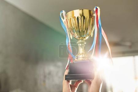 Photo pour Jeune athlète tenant une coupe trophée d'or avec de l'espace prêt pour votre conception de trophée . - image libre de droit