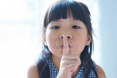girl holding her finger to her lips