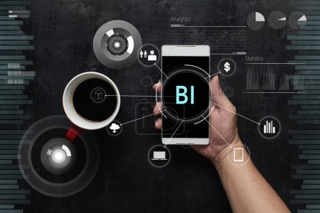 "Man using digital device with ""BI"" word and  fintech infographic icon on virtual screen .Wooden black office desk table on top view ."
